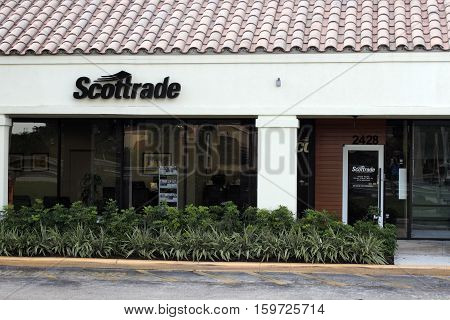 Fort Lauderdale FL USA - April 26 2016: Small outdoor Scottrade sign above a covered walkway. Scottrade sign and office entrance outside during the early morning.