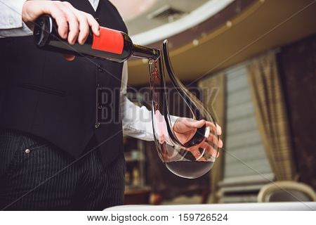 Accurate man is staying and poring crimson beverage in specific glass decanter