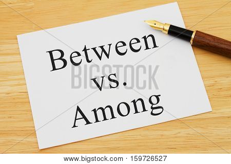 Learning to use proper grammar A white card on a desk with a pen with words Between vs Among