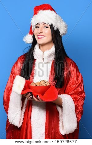 pretty cute sexy santa girl or smiling brunette woman in red sweater and new year hat holds decorative christmas or xmas stocking or boot and chocolate ?hip cookies in bowl on blue studio background