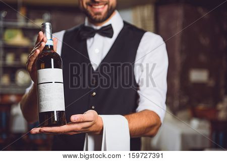 Waiter presenting burnished flask of beverage. Focus on wine