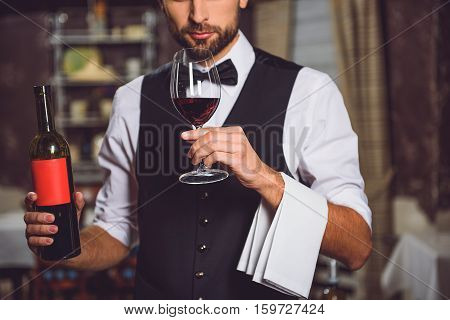 Concentrated sommelier is holding bottle and goblet with beverage. He inhaling