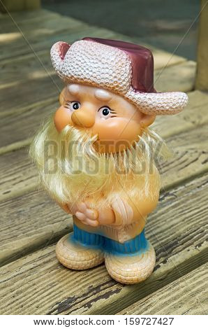 Rubber toy as cheerful Russian peasant in a cap with earflaps