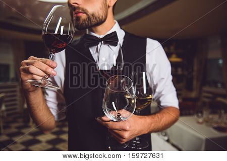 Concentrated sommelier is holding few glasses with different nectar and inhaling sort of wine