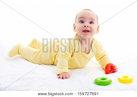 Sweet Baby Is Crawling And Playing With Toys Isolated On White Background