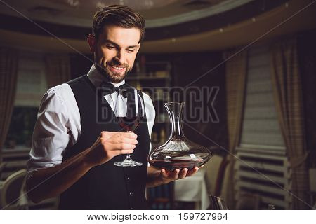 Smiling sommelier is holding carafe and glass with scarlet beverage