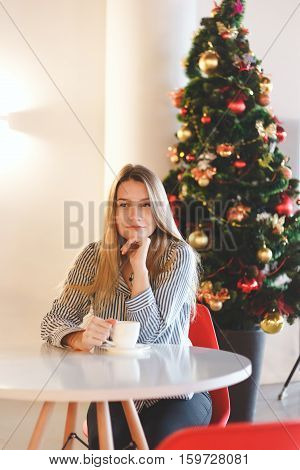 Portrait of a beautiful girl with cup of coffee in cafe Christmas decorations.