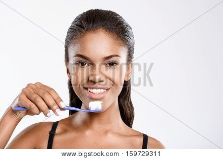 Stay fresh. Smiling girl is brushing her teeth. She is isolated on background