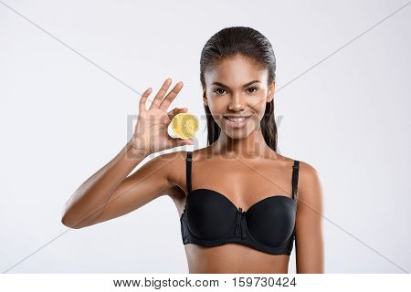 Organic nutrition. Gentle swarthy model is presenting healthy lemon. She is isolated on background