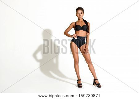 Sensual girl is standing in sexy pose. She put one hand on her waist with confidence. Isolatd and copy space in left side