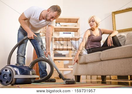 Low view of handsome man using vacuum cleaner and listing to his wife at home. Blond lady saying his husband what to clean first. Family concept.