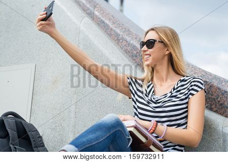 Young pretty girl in sunglasses making selfie photo