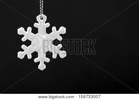 Black and white photo of safety reflector in the form of snowflakes. Necessary equipment to pedestrians for walks during dark conditions
