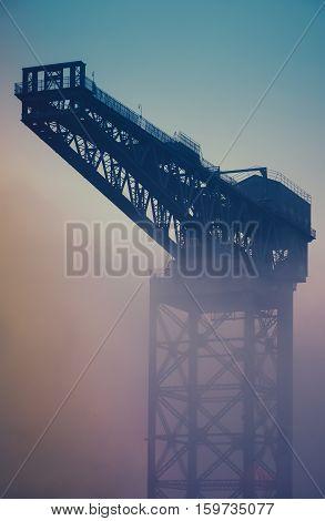Retro Vintage Industrial Shipbuilding Crane In Glasgow Scotland In The Fog At Sunrise