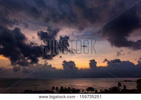 A view of Nha Trang bay in Vietnam at sunrise with a dramatic cloudy sky.