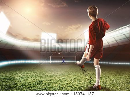Kid boy football player on stadium kicking ball to gates