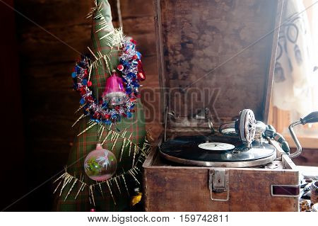 Image of Christmas. Gramophone playing a record. Gramophone with a vinyl record on a background of Christmas decorations, cap, Christmas tree and bright lights.
