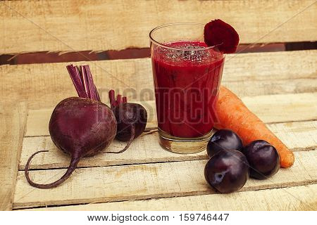 Antioxidant red smoothie or shake with vegetables and fruits including carrot beet plum and chia on wooden background. Healthy food.