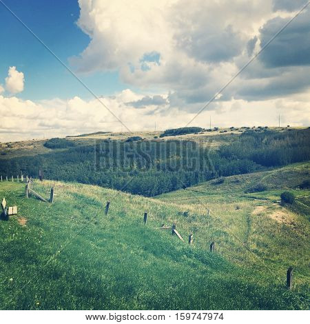 Field landscape in summer.  Lush dark green valley and hills with old wire fence and posts, bright lush green trees and grass. Bright blue sky, dark and white clouds background.
