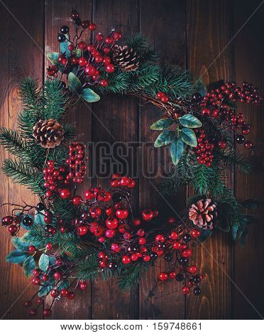 Christmas wreath decoration with pine cones and hawthorn berries on wooden background