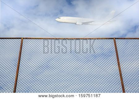 steel fence with plane flying in the sky