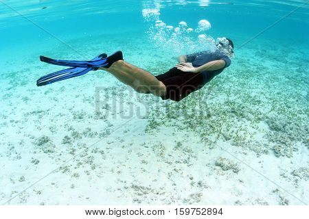 Freediver Asian man in blue rashguard and black shorts with blue fins swim close to white sand and seaweed in clear blue sea Indo-pacific ocean Southeast Asia