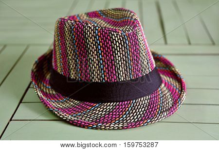 Colorful straw hat on green wooden table