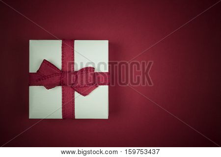 Little white gift box isolated on red background