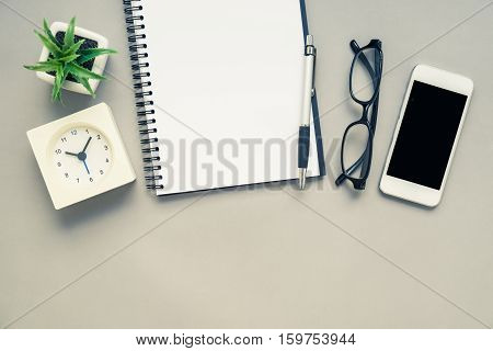 Top view of office desk table with open spiral notebook white alarm clock and mobile phone on grey background with vintage filter