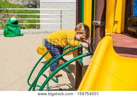 A Boy Climbs On Playground