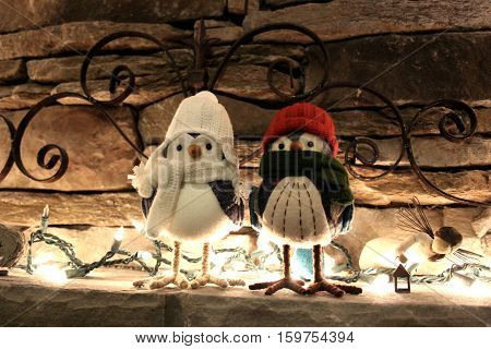 Birds in hats and scarves on the mantle.
