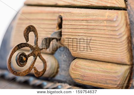 Key in old wooden trunk with metal elements isolated on white background