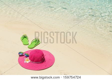 Pink beach hat with flower sunglasses and green slippers in the golden sand by sea shore