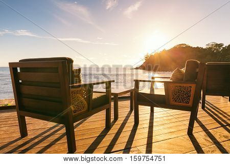 Dining table and two chairs on decking by sea side at evening sun light horizontal composition