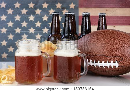 Pint glasses of beer football bowl of potato chips cold beer in bottles on white glass table with United States flag painted on rustic wood. Layout in horizontal format.