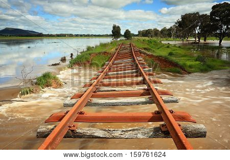 The power of floodwaters in Central West NSW the buckled remains of the rail line as water gushes underneath taking fencing logs and other debris with it and then flows across the road in Crowther. Just a hint of sun highlights the twisted rusty tracks an