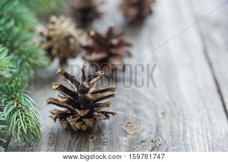 Christmas composition: pine cones and spruce branches on the background of old unpainted wooden boards. Christmas wallpaper