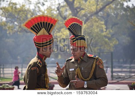 NEW DELHI, INDIA - FEBRUARY 02, 2016 - Two indian guards in uniform talking on the street nearby India gate