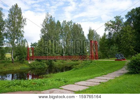 ANDRIANOVO, RUSSIA - JULY 31, 2016: The red suspension bridge through the river Tosna in the cloudy July afternoon. Estate Maryino, Leningrad region