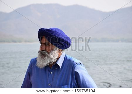 JAIPUR, RAJASTHAN, INDIA - FEBRUARY 05, 2016 - Unidentified indian sikh man with white beard and blue turban beside a lake