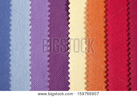 Background of colorful vertical stripes of serrated cotton fabric close up