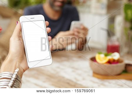 Cropped Shot Of Female Hand Holding Cell Phone With Touchpad, Using App Online During Breakfast. Wom