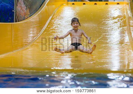 Boy enjoying ride on water slide in Park