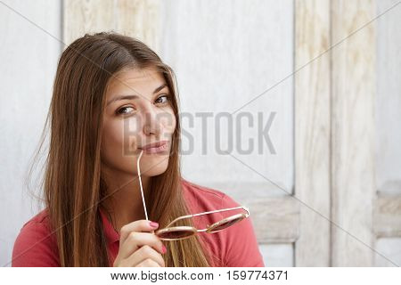 Happy And Joyful Young Caucasian Female With Long Hair Pouting Her Lips, Holding Shades And Touching