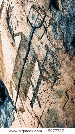 Fragment of Onega petroglyphs figure of demon - prehistoric rock engravings (4th-2nd millennia BC) carved on the granite shore of the lake on the cape Besov Nos.