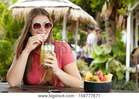 Stylish Young Woman Wearing Round Shades Sitting At Bar Counter And Sipping Fruit Shake With Straw,