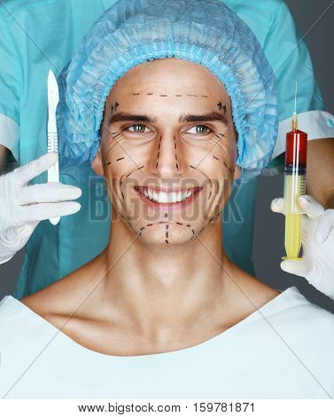 Nurse with syringe and scalpel near the face of scared patient. Happy man with pencil surgical lines (forehead eyes nose cheekbone and jaw). Plastic Surgery concept