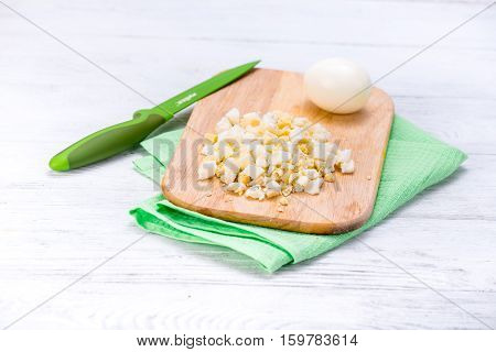 Cooked egg sliced on wooden board. White table with green knife and napkin