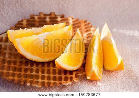 Juicy lobules of an orange lie on homemade waffles