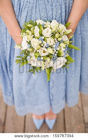 Top view on woman in blue dress holding beautiful wedding bouquet of flowers. Bride.